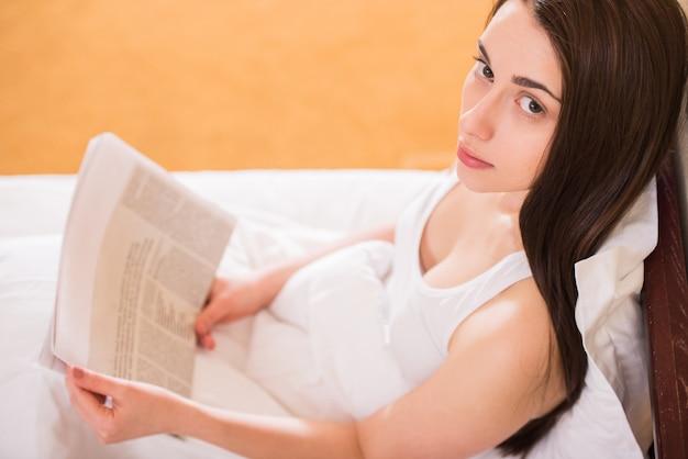 Menina, cama, lendo um jornal