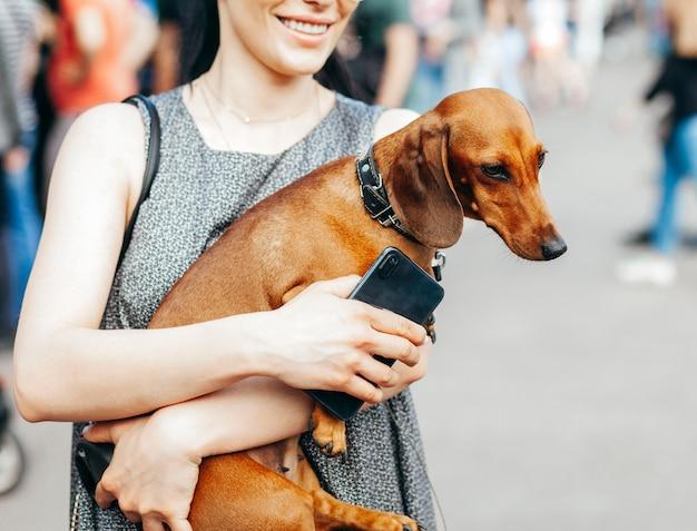 Menina caminha no meio da multidão e segura um adorável cachorro engraçado