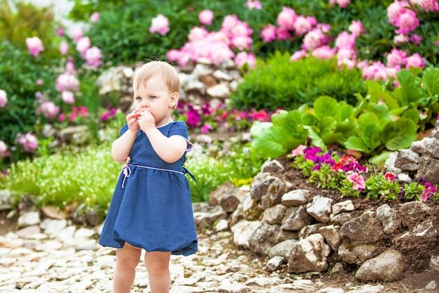 Menina caminha no parque com canteiros de flores