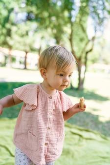 Menina caminhando em um gramado verde com uma panqueca