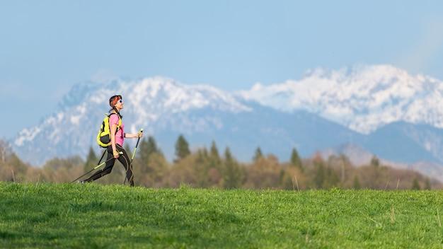 Menina caminhando nas montanhas com contrastes de prados verdes e neve nas montanhas