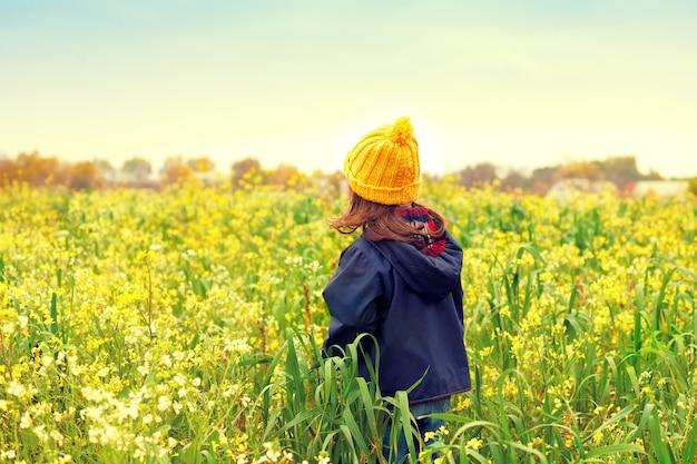 Menina caminhando no prado florido