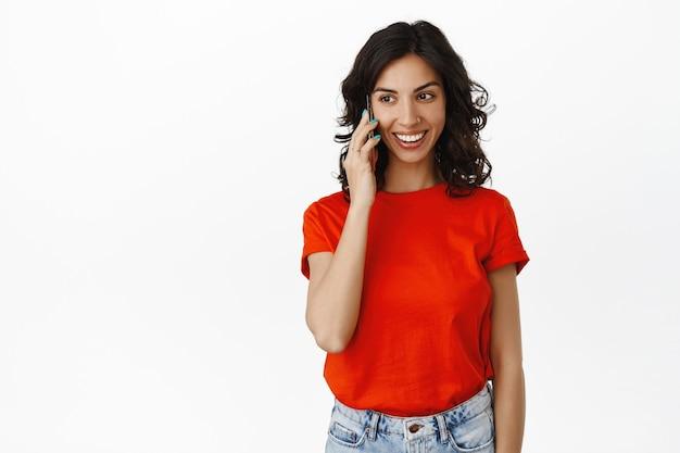 Menina cândida sorridente falando no telefone, conversa feliz, bate-papo com alguém, ligando no smartphone, usando roupas casuais em branco