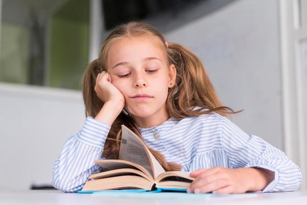 Menina cansada depois de ler na aula