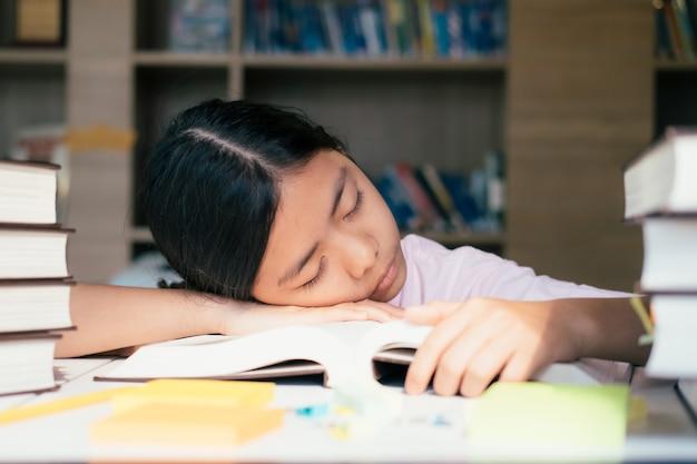 Menina cansada do estudante com os livros que dormem na tabela.