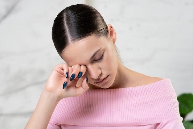 Menina cansada e sonolenta, jovem mulher infeliz exausta e sobrecarregada de trabalho está esfregando, massageando o olho. problemas
