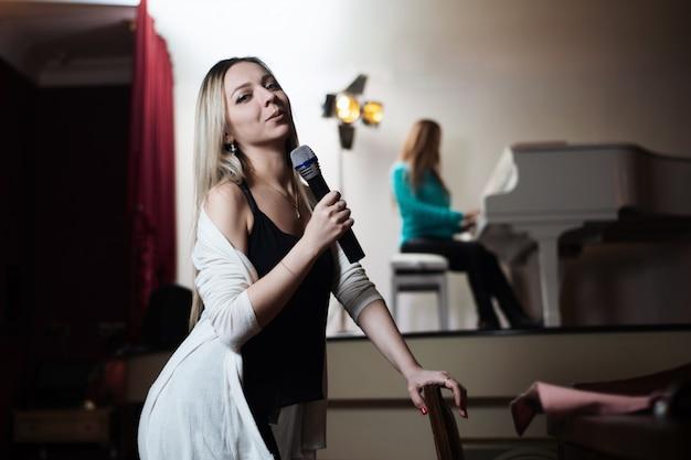 Menina canta em um restaurante e atrás de seu colega toca piano.