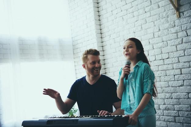Menina canta enquanto pai toca sintetizador.