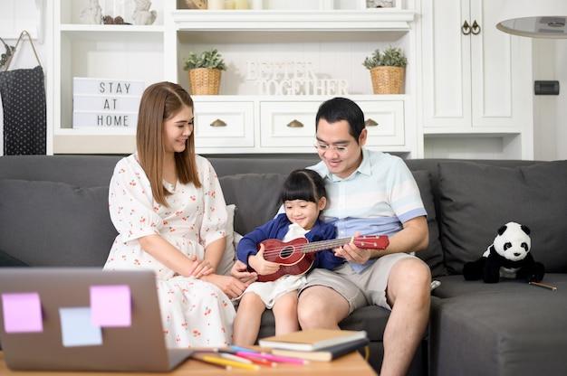 Menina cantando e tocando violão com a família enquanto está sentada no sofá em casa
