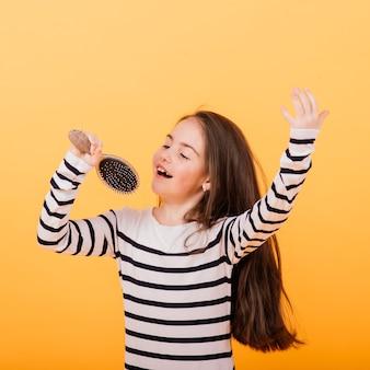 Menina cantando usando uma escova de cabelo como microfone