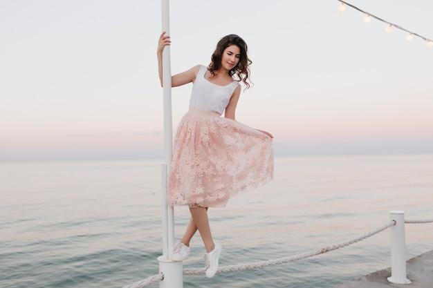 Menina carinhosa e encaracolada em pé na corda e se segurando por um pilar de ferro com o horizonte
