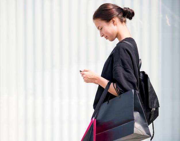 Menina carregando um monte de sacos de compras