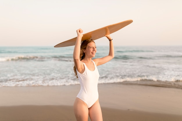 Menina, carregar, tábua corpo, sobre, dela, cabeça, ficar, em, praia arenosa