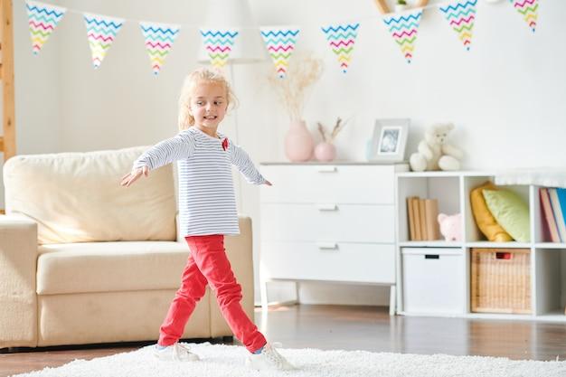 Menina casual de pulôver e jeans vermelho esticando os braços enquanto dava passos de dança no tapete branco macio