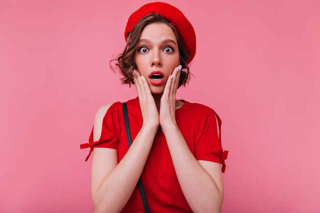 Menina cativante espantada com cabelo castanho ondulado olhando. retrato interno da adorável francesa expressando emoções surpresas.