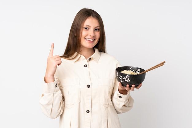 Menina caucasiana adolescente isolada na parede branca, apontando para cima uma ótima idéia, mantendo uma tigela de macarrão com pauzinhos