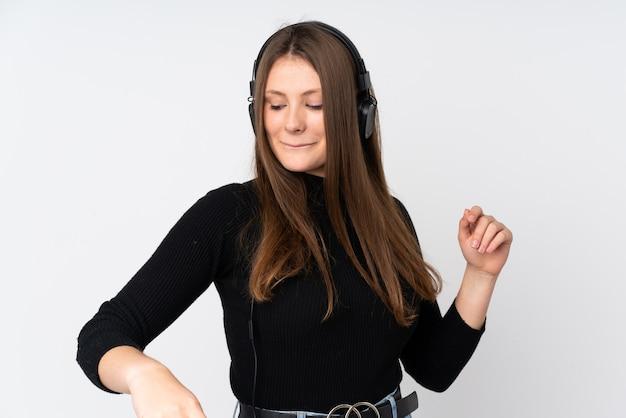 Menina caucasiana adolescente isolada na parede branca, ouvir música e dançar