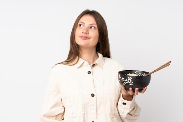 Menina caucasiana adolescente isolada no branco olhando para cima enquanto sorrindo enquanto segura uma tigela de macarrão com pauzinhos