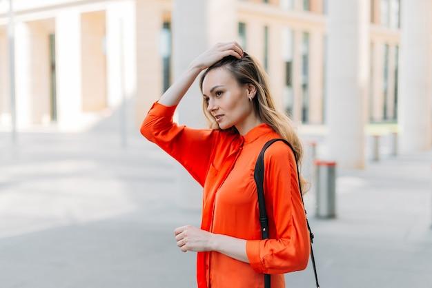 Menina caucasiana andando pela cidade com uma bolsa no ombro