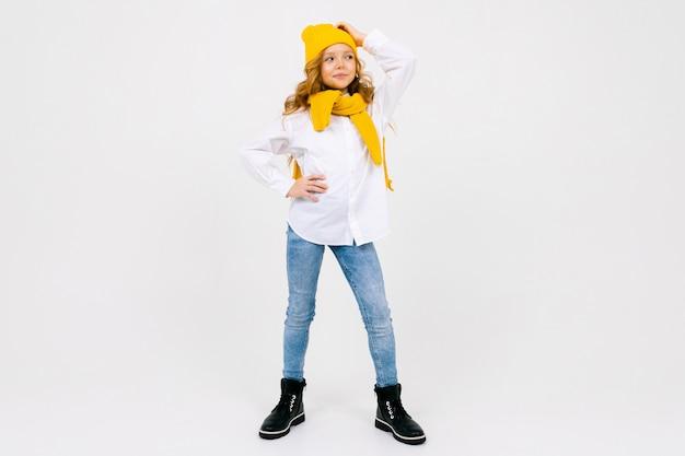 Menina caucasiana atraente elegante em uma camisa branca e calça jeans azul e um chapéu amarelo em pleno crescimento posando no estúdio branco com espaço de cópia