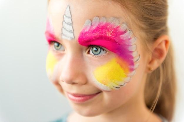 Menina caucasiana bonita com pintura facial de unicórnio