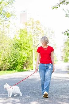 Menina caucasiana caminhando no parque com seu gato