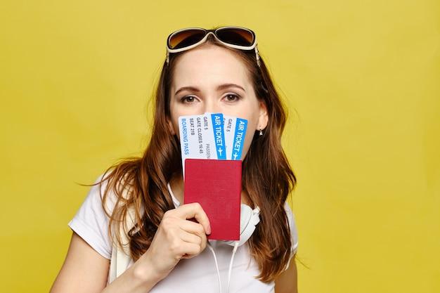 Menina caucasiana cobre metade do rosto com passagens aéreas e passaporte em um fundo amarelo.