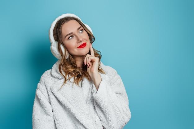 Menina caucasiana com batom vermelho, vestida com um casaco de pele sintética de inverno branco e fones de ouvido de pele, está pensativa e olha para o lado no espaço de cópia para texto isolado na parede azul