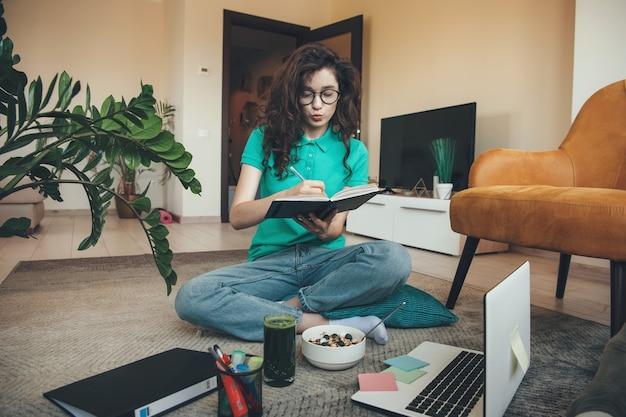 Menina caucasiana com cabelo encaracolado dando aula on-line no chão em frente ao laptop enquanto come cereais e suco verde fresco