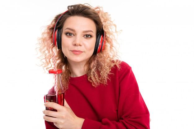 Menina caucasiana com cabelo loiro encaracolado bebe suco e ouve música, retrato isolado