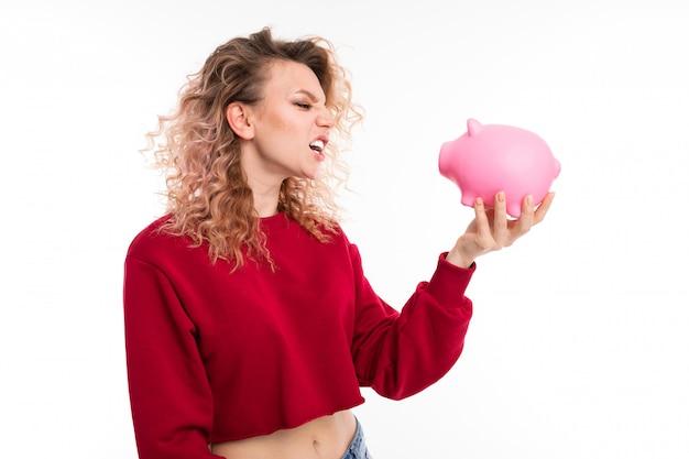 Menina caucasiana com cabelo loiro encaracolado mantém um mealheiro de porco rosa, retrato isolado
