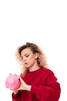 Menina caucasiana com cabelo loiro encaracolado, tentando obter dinheiro com o mealheiro de porco rosa, retrato isolado