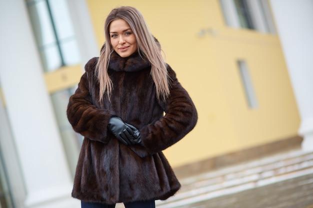 Menina caucasiana, com cabelos longos, grandes olhos lindos com casaco de pele de inverno no parque