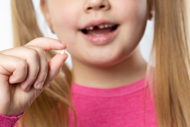 Menina caucasiana com longos cabelos loiros em roupas cor de rosa segura um dente de leite arrancado e sorri. conceito de higiene dental