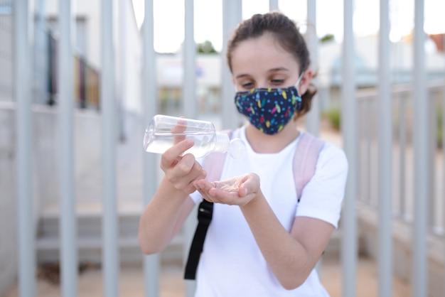 Menina caucasiana com máscara derramando gel hidroalcoólico nas mãos na porta da escola no novo normal