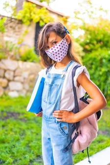 Menina caucasiana com máscara facial pronta para voltar para a escola. nova normalidade, distância social, pandemia de coronavírus, covid-19. jaqueta, mochila e um bloco azul para anotações em mãos