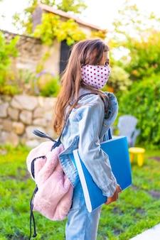 Menina caucasiana com máscara facial pronta para voltar para a escola. nova normalidade, distância social, pandemia de coronavírus, covid-19. jaqueta, mochila, máscara com pontos rosa e um bloco azul na mão