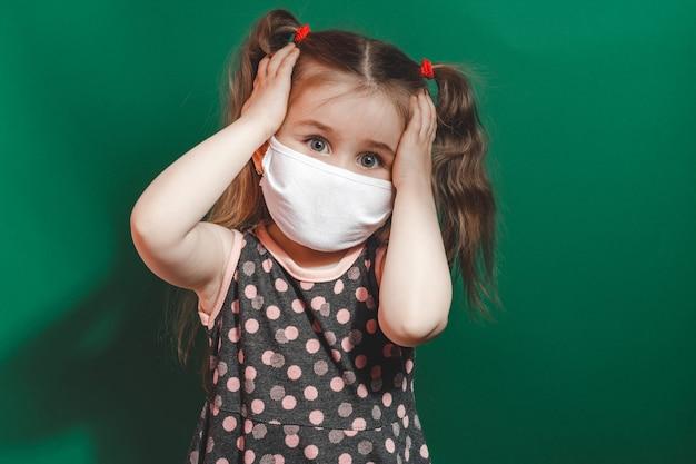 Menina caucasiana com máscara médica usa vestido de bolinhas vermelhas em estúdio sobre fundo verde e segura a cabeça com dor.