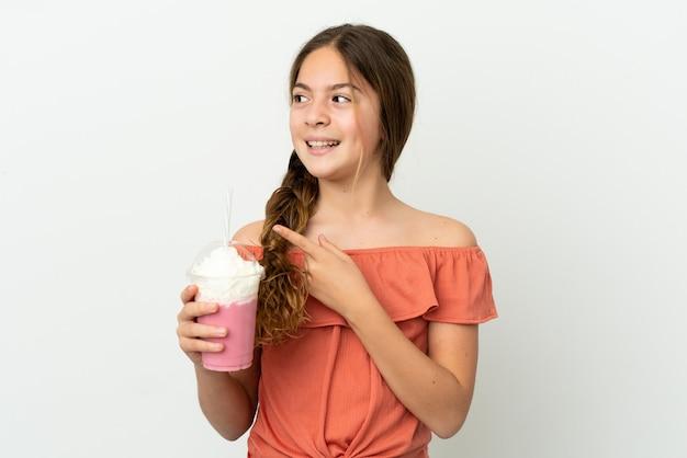 Menina caucasiana com milk-shake de morango isolado no fundo branco com a intenção de descobrir a solução enquanto levanta um dedo
