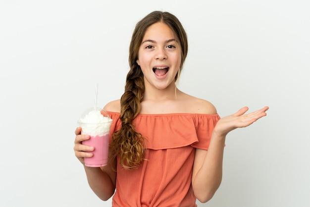 Menina caucasiana com milk-shake de morango isolado no fundo branco com expressão facial chocada