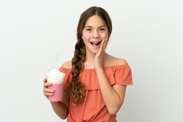 Menina caucasiana com milk-shake de morango isolado no fundo branco com expressão facial surpresa e chocada