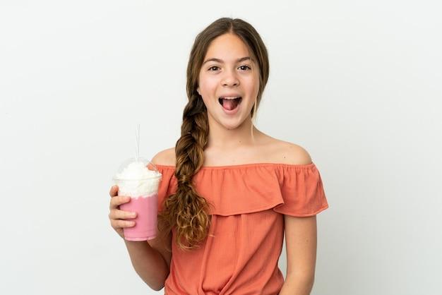 Menina caucasiana com milk-shake de morango isolado no fundo branco com expressão facial surpresa