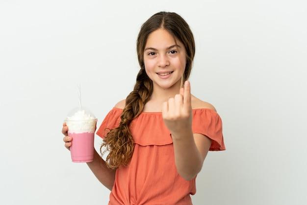 Menina caucasiana com milk-shake de morango isolado no fundo branco fazendo gesto de aproximação