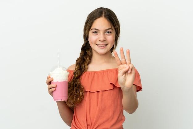 Menina caucasiana com milk-shake de morango isolado no fundo branco feliz e contando três com os dedos
