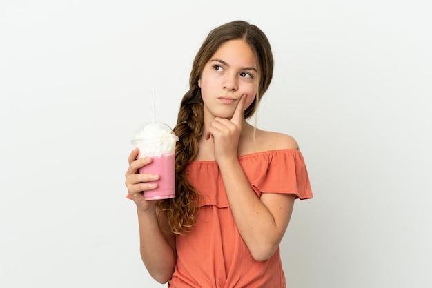 Menina caucasiana com milk-shake de morango isolado no fundo branco tendo dúvidas enquanto olha para cima