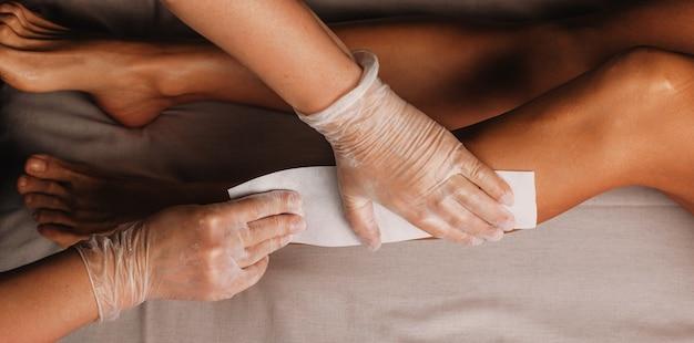 Menina caucasiana com pernas bonitas está fazendo tratamento anti-envelhecimento com profissionais