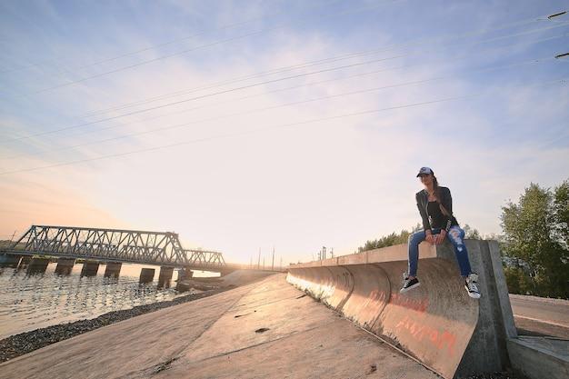 Menina caucasiana com pernas longas em jeans e boné de beisebol ao pôr do sol
