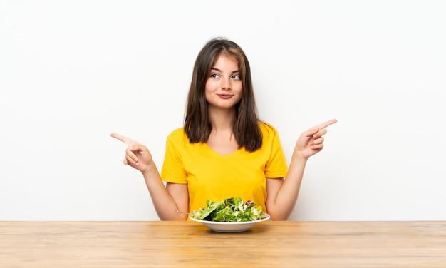 Menina caucasiana com salada, apontando para as laterais, tendo dúvidas