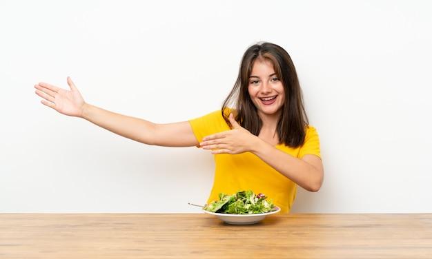 Menina caucasiana com salada, estendendo as mãos para o lado para convidar para vir