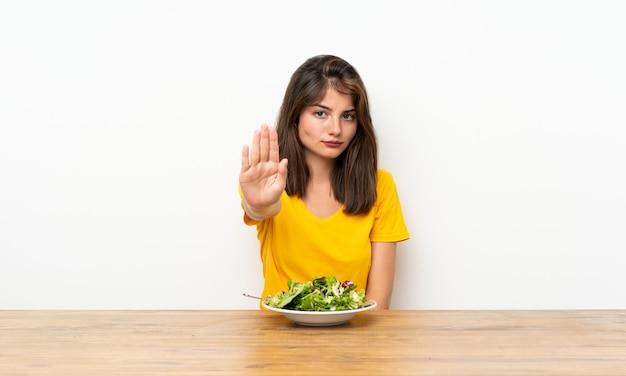 Menina caucasiana com salada, fazendo o gesto de parada com a mão
